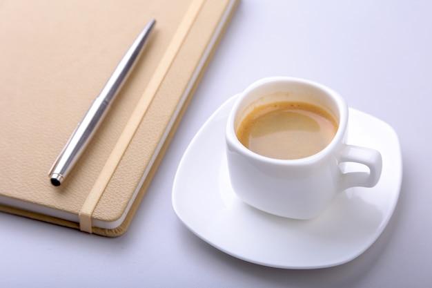 Стильный блокнот, шариковая ручка и белая чашка с ароматным кофе эспрессо на офисном столе.