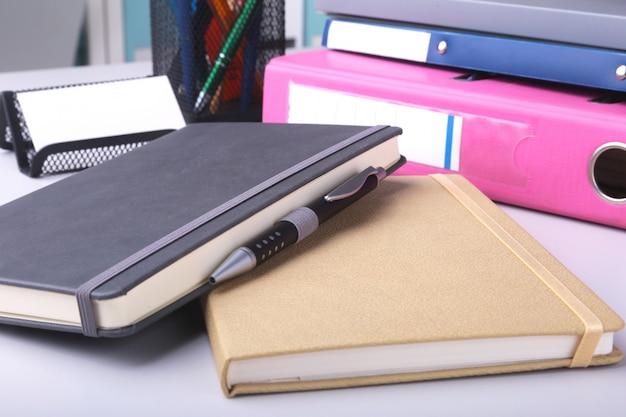 机の上のフォルダーファイル、メモ、ペン。背景をぼかし。