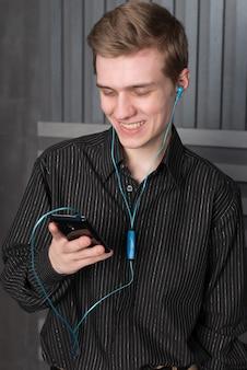 若い男があなたのスマートフォンから音楽を聴く