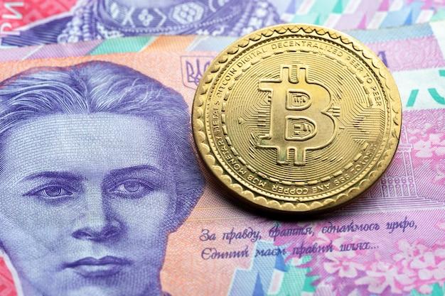 Символ биткойн на фоне украинской бумажной валюты. концепция криптовалютных технологий.