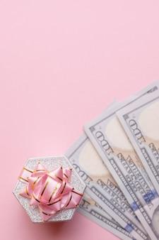 ギフト用の箱はピンクの背景で現金ドルの上に立ちます。