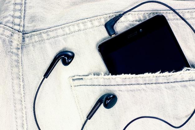 スマートフォンとヘッドフォンとジーンズのポケットへのクローズアップ