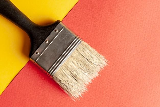 黄色と赤の紙の背景にペイントブラシ
