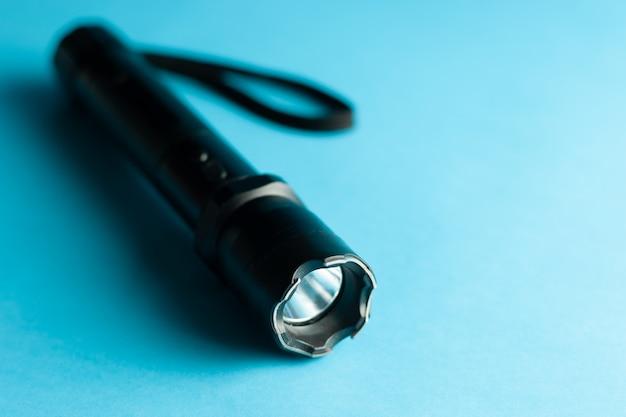 Черный металлический фонарик с шокером на синем фоне