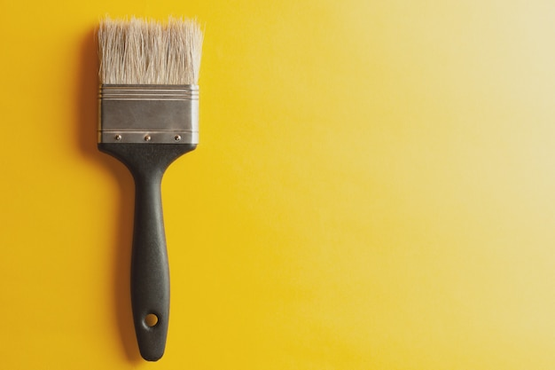 黄色の背景にペイントブラシ。創造的なコンセプトです。デザインや装飾用