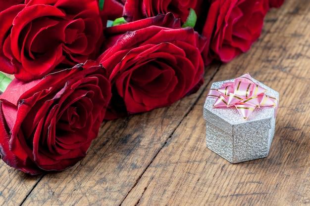 ピンクのリボンと赤いバラの背後にあるギフトボックス