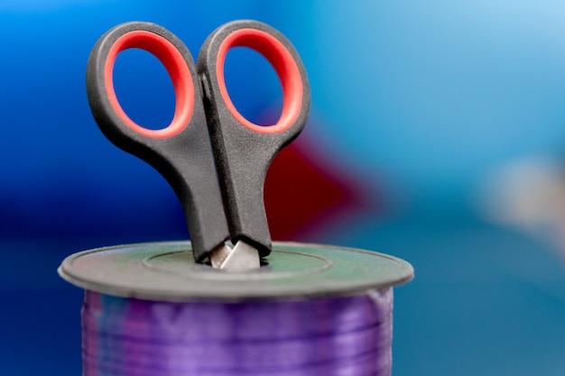Ножницы и фиолетовый васи ленты на размытым разноцветным фоном.