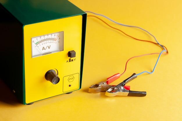 携帯用カーバッテリー充電器。赤と黒のクリップで充電器を閉じます。黄色の背景充電放電装置