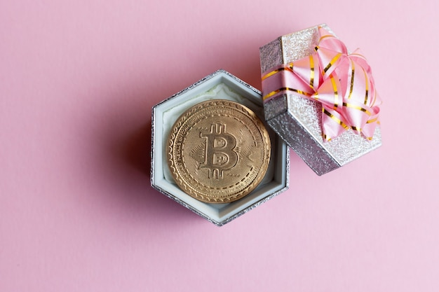 Биткойн лежит в небольшой подарочной коробке на розовом фоне.