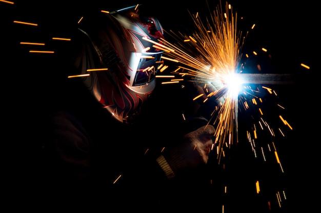 金属溶接を実行するマスクの男性溶接機。濃い色の写真。飛ぶ火花。