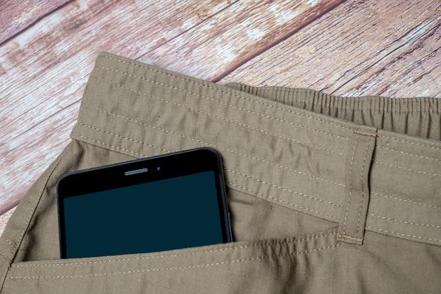 ポケットから突き出ている黒いスマートフォン