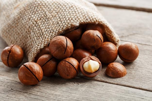 袋に木製のテーブルにマカダミアナッツ