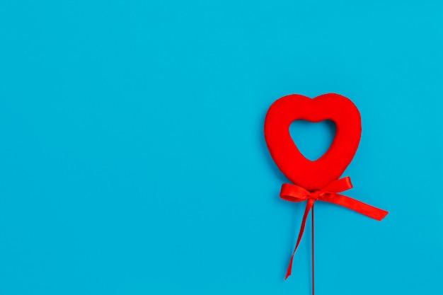 青い表面、愛、バレンタインの日に弓で赤いハート