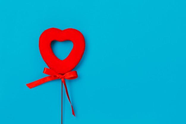 Красное сердце с бантом на синей поверхности, любовь, день святого валентина
