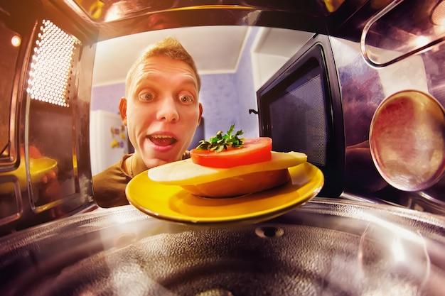 幸せな男がサンドイッチを電子レンジに入れる