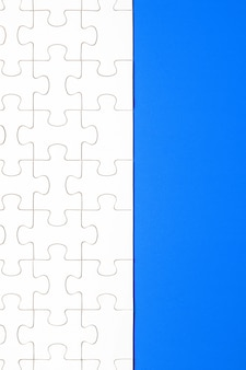 Белые кусочки головоломки на синем фоне. фон для контента