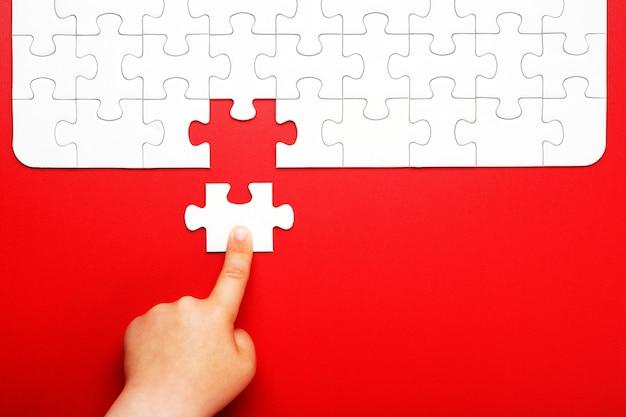 子供の手が赤い背景に白いパズルのピースを移動します
