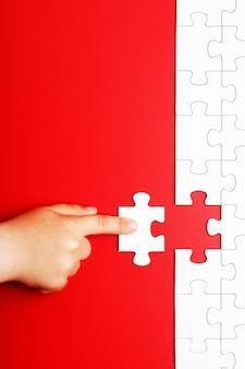 Детская рука двигает кусок белой головоломки на красном фоне