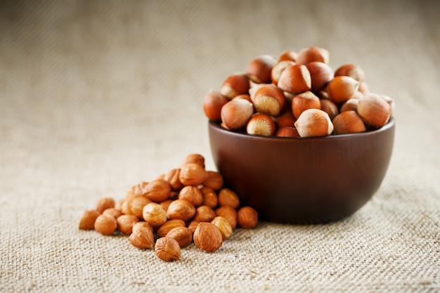 Очищенные орехи в деревянной, темно-коричневой чашке на ткани мешковины. супер еда, сырье.