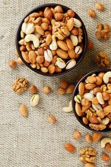 黄麻布の生地に対して木製のカップにさまざまなナッツを混ぜます。構造および背景、マクロとしてのナット。上面図。