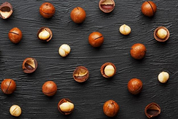 黒のテクスチャ石の背景に精製されたシェルはマカデミアナッツを繰り返します。健康的な食事のコンセプト