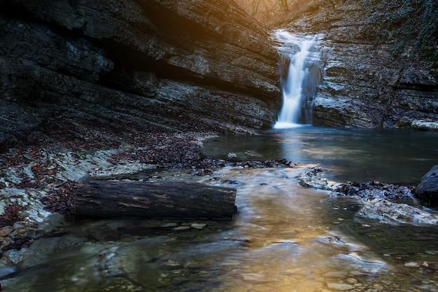 赤とオレンジ色のカラフルな秋の森の山川の美しい滝は日没で残します。自然の風景