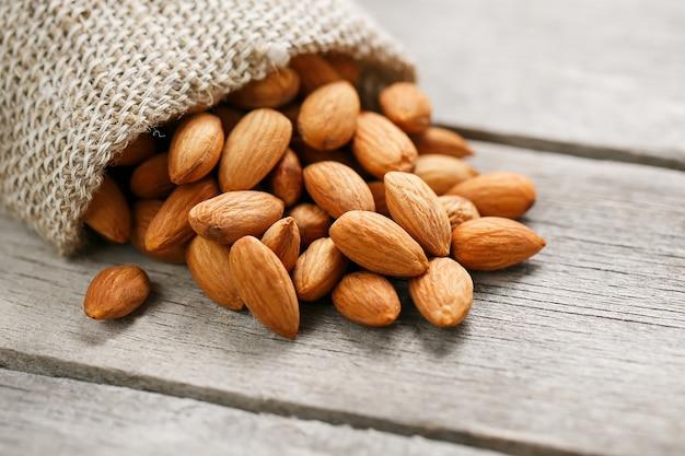 Миндальные орехи в мешковину на деревянный серый.