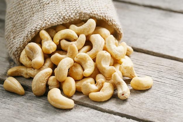 木製の灰色の黄麻布の袋にカシューナッツ。健康食品