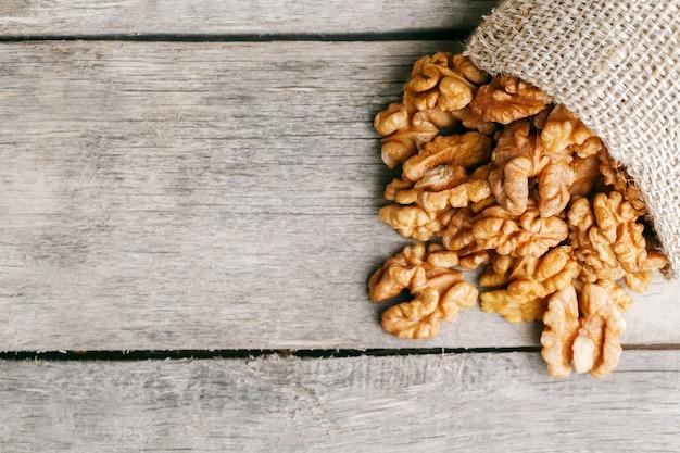 Грецкие орехи в мешковину на деревянный серый.