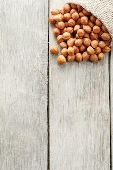 灰色の木製テーブルの黄麻布の袋に彫られたヘーゼルナッツ。オーガニックの新鮮な収穫
