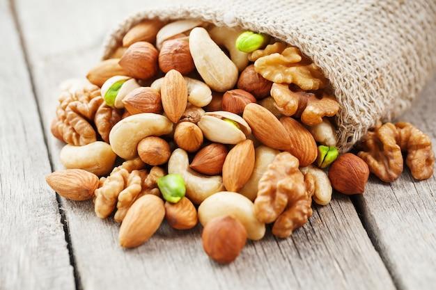 黄麻布の生地に対して木製カップで異なるナッツを混ぜます。構造および背景、マクロとしてのナット。上面図。
