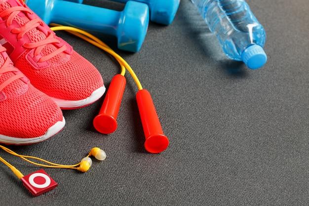 スポーツ用品、ダンベル、縄跳び、水のボトル、スニーカー、プレーヤーの平面図。グレーに分離