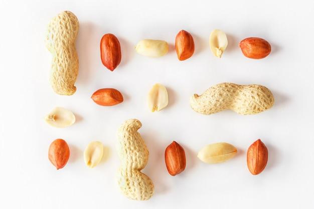 白で隔離されるピーナッツ。皮をむいた皮とスカーラップ。