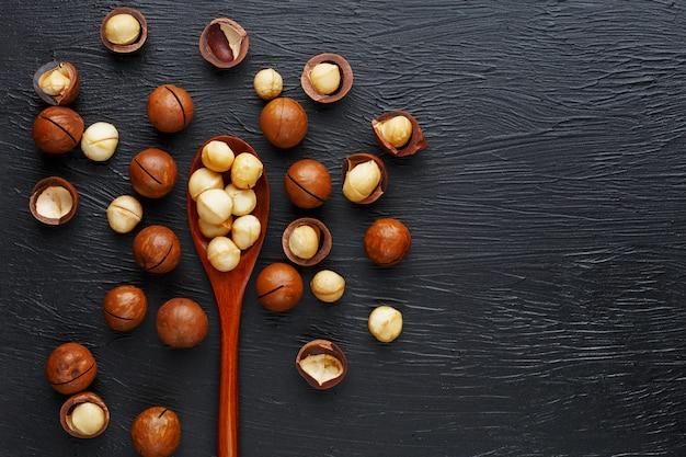 殻付きマカダミアナッツと皮をむいたマカダミアナッツ、木のスプーンで黒のテクスチャ背景