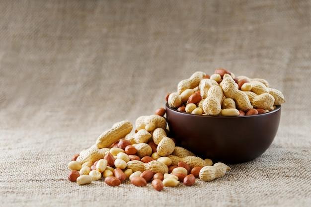 殻に落花生とカップに皮をむいたクローズアップ。殻にローストピーナッツを入れ、茶色の布で皮をむいた。