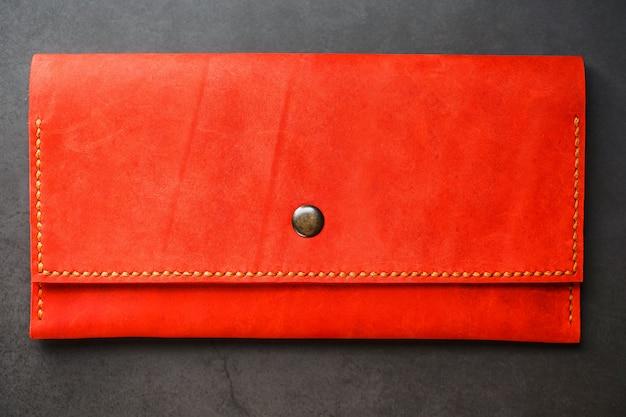 Красный кожаный кошелек на темном фоне вид сверху. крупный план, информация о кошельке, заклепка и прошивка