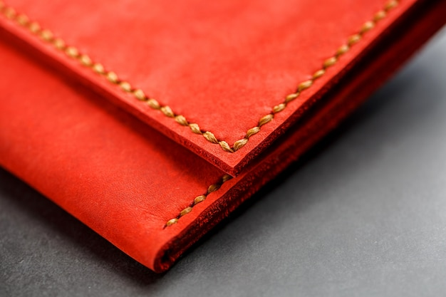 暗い背景の上面に赤い革の財布。クローズアップ、財布の詳細、リベットとファームウェア