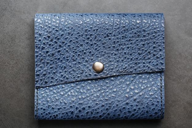 Синий кожаный кошелек на темном фоне вид сверху. крупный план, информация о кошельке, заклепка и прошивка