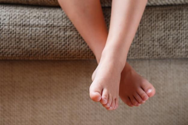 Детские ноги крупным планом свисают с дивана в комнате. детские пальцы ног, пока ребенок сидит на кресле