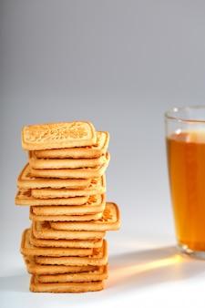 黄金の小麦のクッキーのスタックと香りのよい緑茶イオングレーのマグカップ