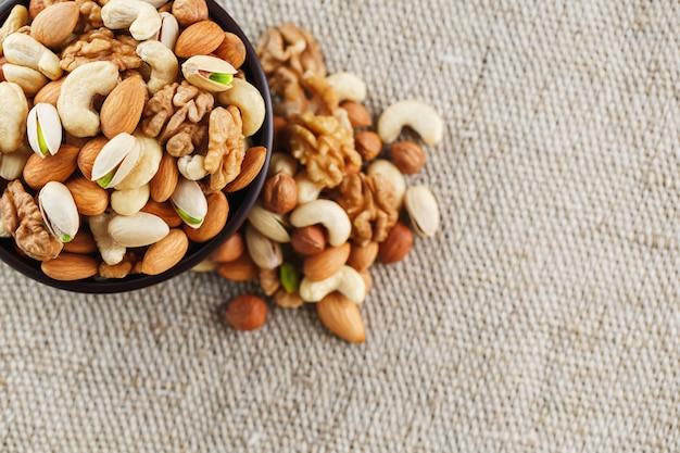黄麻布の生地を背景に木製カップで異なるナッツのミックス