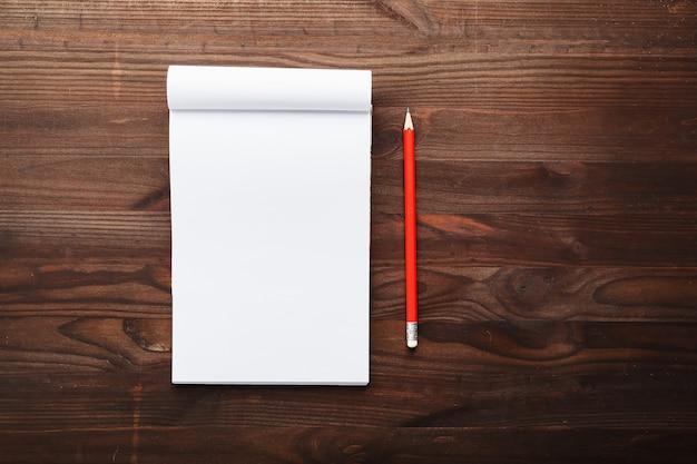 教育のため、茶色の木製のテーブル背景に赤鉛筆でメモ帳を書く目標と行為