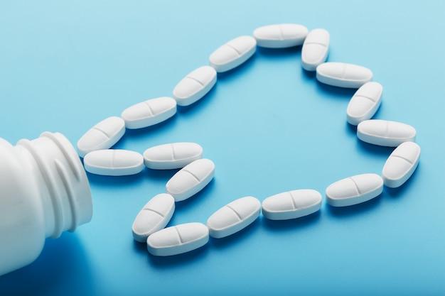 青色の背景にカルシウムと白いビタミンで作られた歯