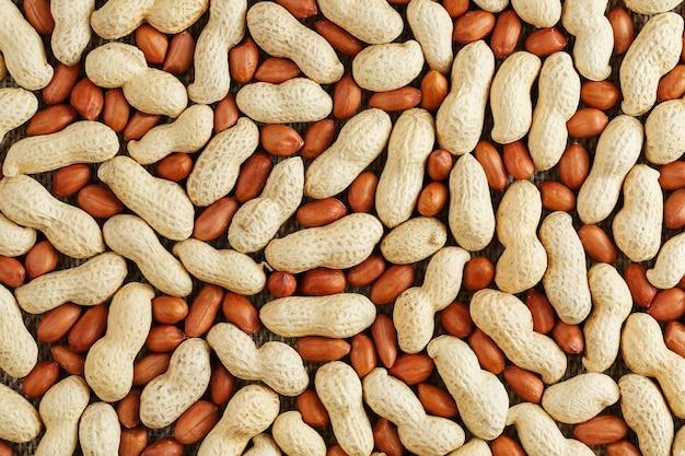 皮をむいたシェルでピーナッツ、豆の食品背景のテクスチャ