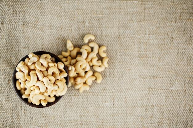 黄麻布の背景に木製のボウルにカシューナッツ
