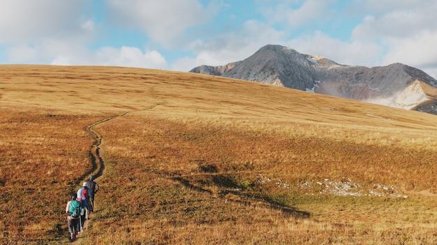 遠くに観光客や旅行者がいる雄大な風景を通る山頂や丘を通るルート。