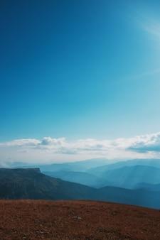 青い空と雲のある風景、雄大な山頂と丘を通るルート