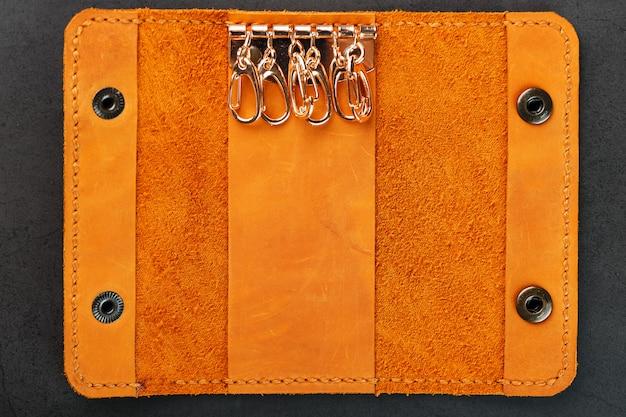 本物のヌバックレザー製の鍵のための茶色のカバーウォレット。手作りのリベットと縫い目のクローズアップ