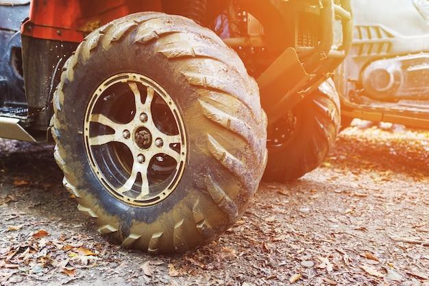 Квадроцикл в лесу, в грязи. колеса и элементы квадроцикла крупным планом в грязи