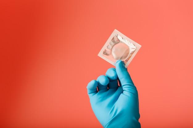青い手袋の医者の手は、パッケージにコンドームを保持しています。精子ラテックスと妊娠に対する保護。